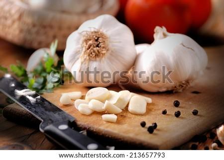 sliced garlic on wooden chopping board