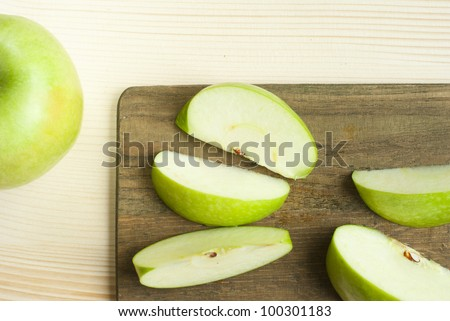 sliced green apple on wooden cutting board