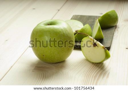 sliced green apple on wooden cutting board