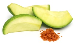Sliced green mango with chili powder and salt over white background