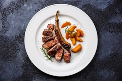 Sliced grilled beef rib on bone on white plate with potato wedges on dark background