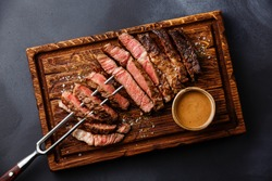 Sliced grilled meat steak Rib eye on meat fork and Pepper sauce on dark background