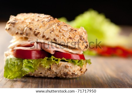 Sliced ham sandwich with tomatoes on a mixed seed bread