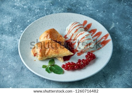 Sliced homemade berry strudel served with fresh red currant berries and powdered sugar on an old background on a plate with ice cream pic
