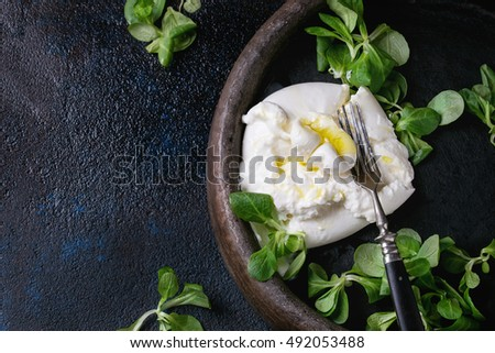 Sliced Italian cheese burrata with vintage fork, fresh corn salad and olive oil in clay tray over dark textural background. Overhead view #492053488
