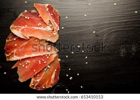 Shutterstock Sliced jamon and sesame seeds on a blackwood background. Parma ham / hamon on a black background with sesame seeds with space for a textual top view. Jamon Serrano / Iberico. Traditional Spanish ham