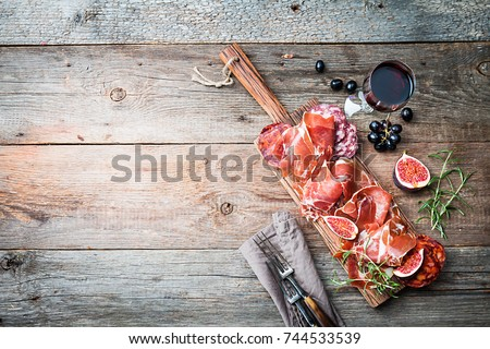 Shutterstock Sliced jamon on cutting board with fig?, grapes and red wine. Parma ham / hamon on wooden background with copy space, top view. Jamon Serrano / Iberico. Traditional Spanish ham