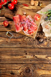 Sliced jamon on cutting board with tomato
