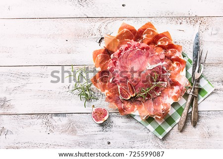 Shutterstock Sliced jamon on white plate. Parma ham / hamon on wooden background with fig and grapes with copy space, top view. Jamon Serrano / Iberico. Traditional Spanish ham