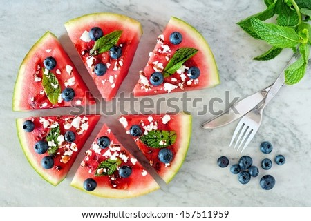Sliced, juicy watermelon pizza with blueberries, feta, mint and balsamic glaze, above view on marble