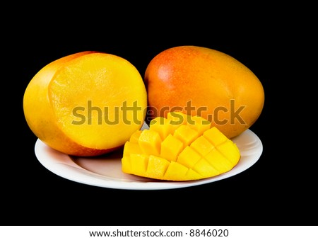Sliced large mango fruits, on white plate, black background