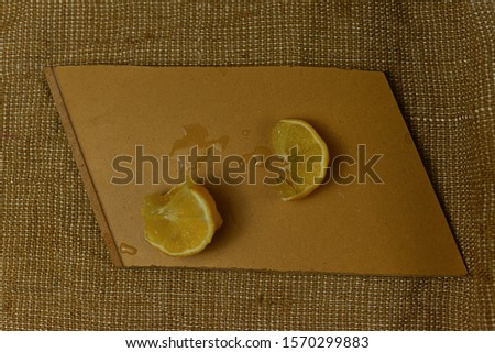 sliced lemon on wooden desk isolated on burlap cloth. popular citrus fruit. photo of fruit which fights with acidification of humans body, promotes alkalization of the body and enhances immunity
