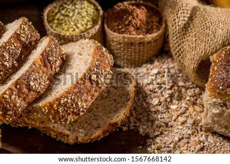 sliced loaf bread made with sesame seeds, sunflower seeds,  linsced, oatmeal, barley, rye, chia, pumpkin seed, poppy, nutmeg, on rustic wooden table with other breads and ingredients in background.