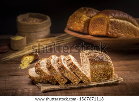 sliced loaf bread pão de forma made with sesame seeds, sunflower seeds,  linsced, oatmeal, barley, rye, chia, pumpkin seed, poppy, nutmeg, with other breads and ingredients in background.