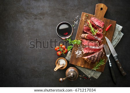 Sliced medium rare grilled beef ribeye steak on cutting board on dark background #671217034