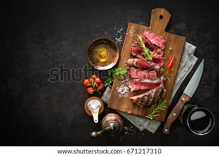 Sliced medium rare grilled beef ribeye steak on cutting board on dark background #671217310