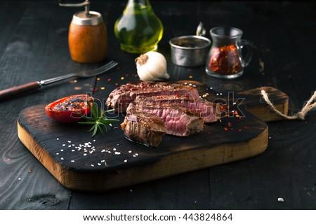 Sliced medium rare grilled Steak Ribeye with rosemary on a dark background