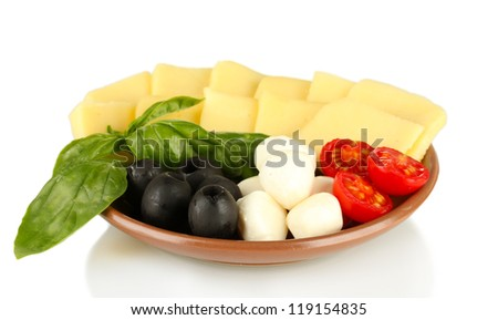 sliced mozzarella cheese with vegetables in the plate isolated on white
