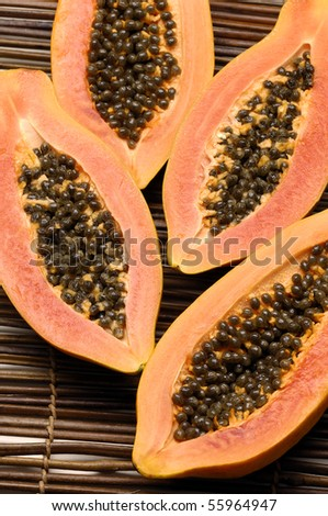 Sliced of half papaya on bamboo mat