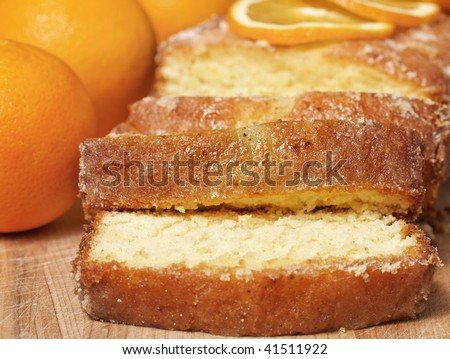 sliced orange bread dessert with sugar icing on a wooden cutting board. Very shallow depth of field.