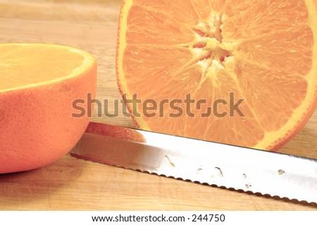Sliced Orange on a Cuttingboard With a Knife.
