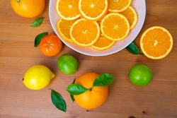 Sliced oranges laying in big plate. Fresh mandarins, limes, lemons with leaves on wooden desk near bowl. Top cropped view. Studio shot. Nutrition and vegetarian concept