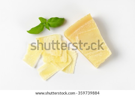 sliced parmesan cheese and basil on white background