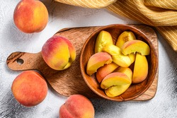 Sliced Peaches, organic fruit in a wooden bowl. Gray background. Top view