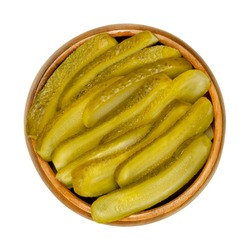 Sliced pickled cucumbers, also known as pickle or gherkin, in a wooden bowl. Small pickled cucumbers with bumpy skin, sliced lengthways. Baby pickles. Close-up from above over white, macro food photo.