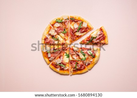 Sliced pizza prosciutto with parmesan and arugula on pink background. Pizza ham and cheese in equal slices top view. Italian traditional food.