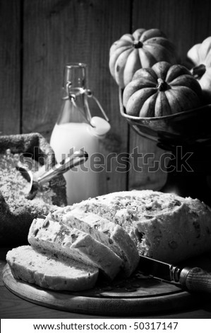 Sliced pumpkin bread in rustic farmhouse setting with old fashioned weighing scales in black and white