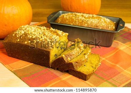 Sliced pumpkin bread with pan and pumpkins