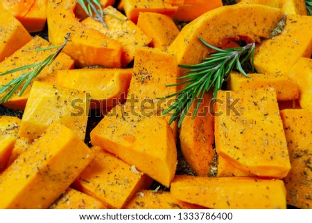 Sliced pumpkin Butternut squash, sprinkled with seasoning. With sprigs of rosemary. For baking. Macro picture.