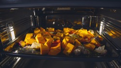Sliced pumpkin with thyme, olive oil, salt, garlic and onion on dripping pan in oven. Close up of delicious spiced pumpkin baking on pan in electric oven. Culinary and cooking concept