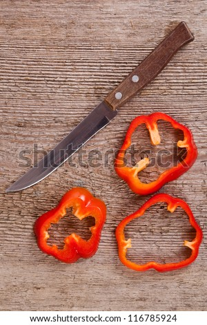 sliced red bell peppers and old knife on rustic wooden table - stock photo