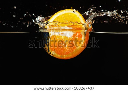 Sliced ripe orange falling into the water with a splash on a dark background
