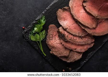 sliced  roast beef on slate board, black background, top view #1033652083