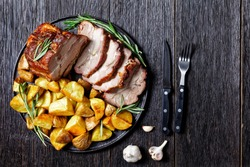 Sliced roasted pork loin served with baked potato wedges, rosemary  on a plate with garlic steak cutlery on a dark wooden background, top view, close up