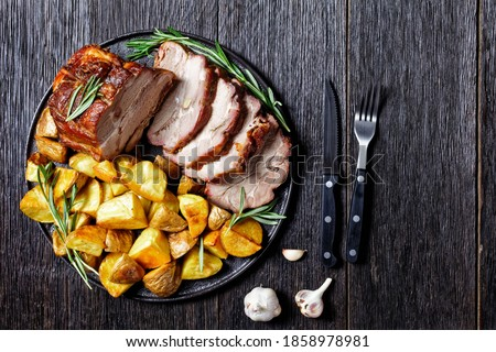 Sliced roasted pork loin served with baked potato wedges, rosemary  on a plate with garlic steak cutlery on a dark wooden background, top view, close up Stockfoto ©