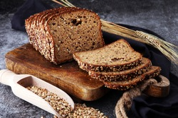 Sliced rye bread on cutting board. Whole grain rye bread with seeds