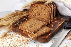 Sliced rye bread on cutting board. Whole grain rye bread with seeds on rustic background