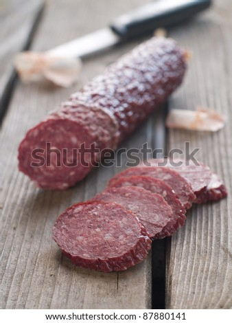 Sliced salami on rustic wooden table, selctive focus