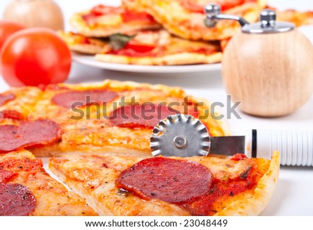 sliced salami pizza on white, a pizza knife, a wooden pepper-box, and sliced pizza margherita in the back