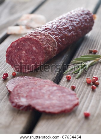 Sliced salami with pepper and rosemary on rustic wooden table, selective focus