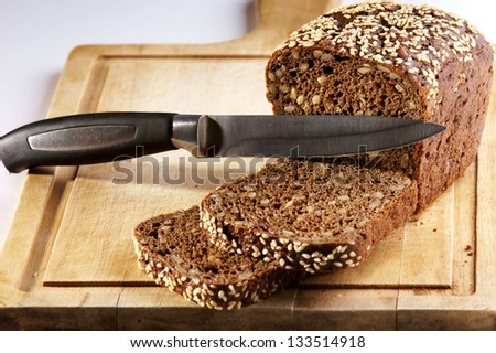 sliced sesame seeds bread on wooden chopping board