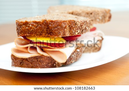 sliced smoked turkey breast with heirloom tomatoes on fresh and healthy organic seed bread