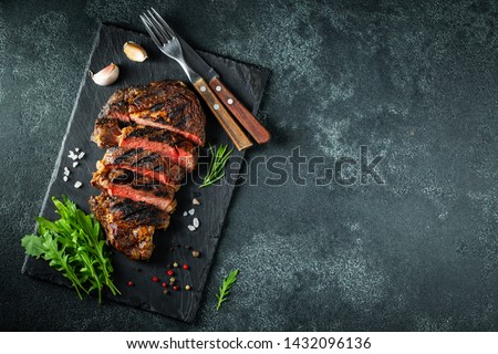 Sliced steak ribeye, grilled with pepper, garlic, salt and thyme served on a slate cutting Board on a dark stone background. Top view with copy space. Flat lay