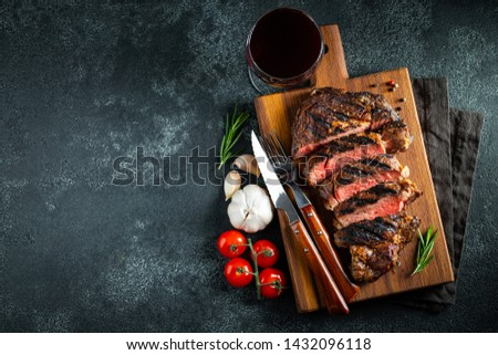 Sliced steak ribeye, grilled with pepper, garlic, salt and thyme served on a wooden cutting Board on a dark stone background. Top view with copy space. Flat lay