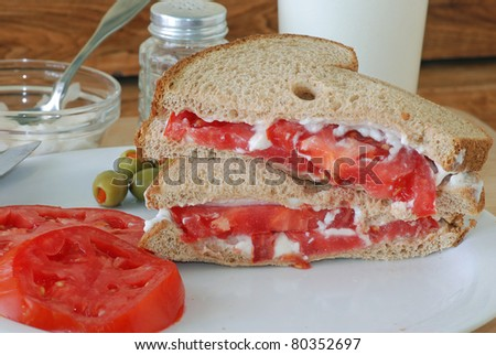 Sliced tomato and mayonnaise on multi-grain bread with stuffed olives and glass of cold milk.