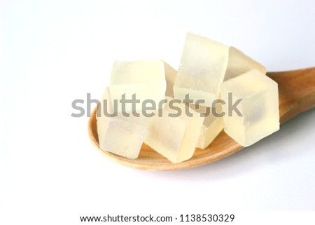 Sliced transparent melt and pour glycerin soap bases, material for homemade soap, on wooden paddle on white background.